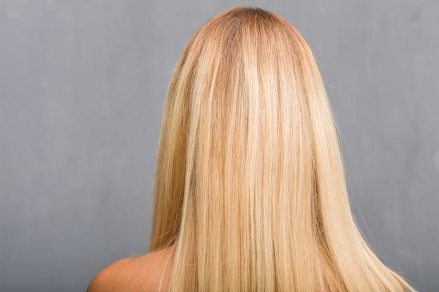 顔のクローズアップ、背中を見せて自然な若いブロンドの女性の肖像画
