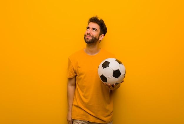 目標と目的を達成することを夢見て若いサッカー選手男