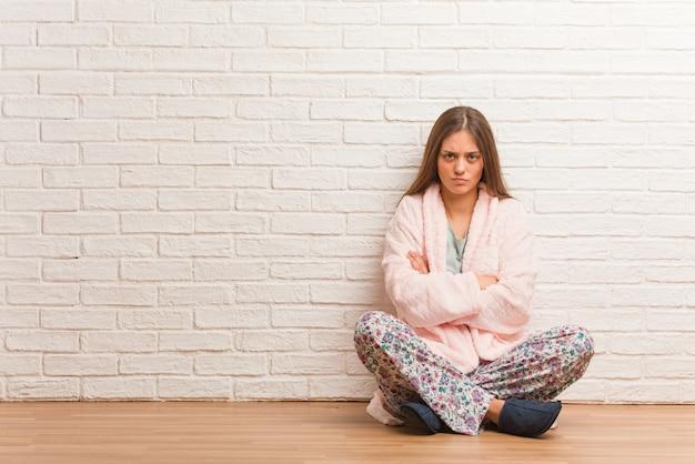 Расслабленной руки скрещивания пижамы молодая женщина