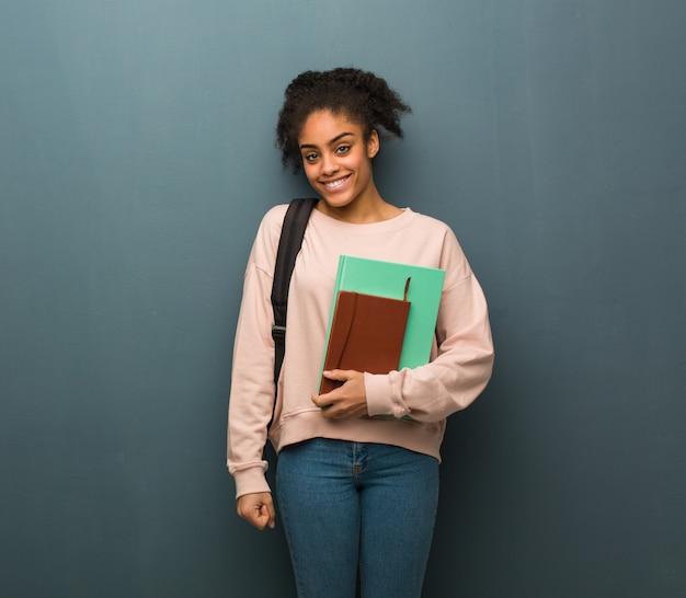 大きな笑顔で陽気な若い学生黒人女性。彼女は本を持っています。