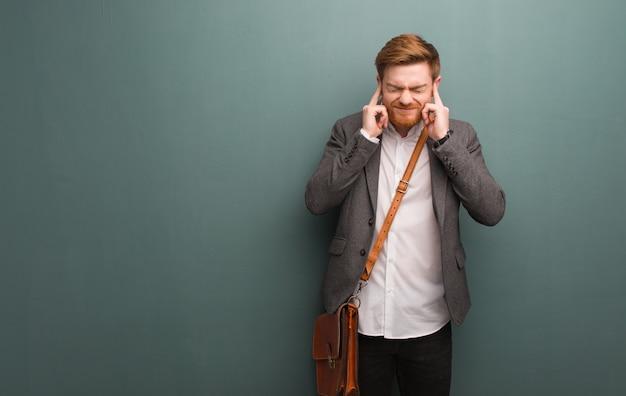 手で耳を覆っている若い赤毛のビジネスマン