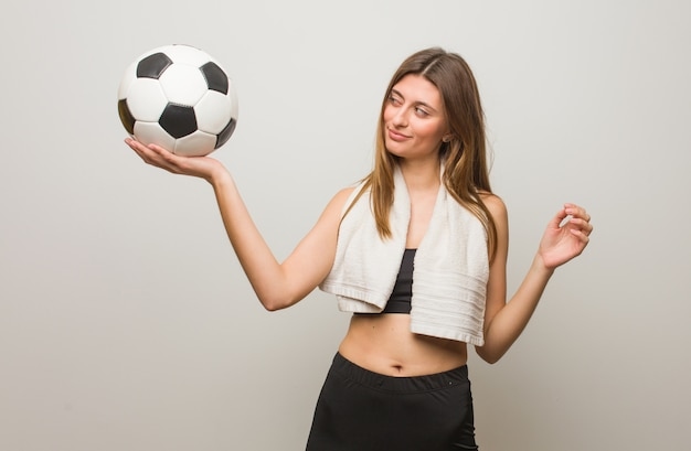スパイグラスのジェスチャーを作る若いフィットネスロシア女性。サッカーボールを保持しています。