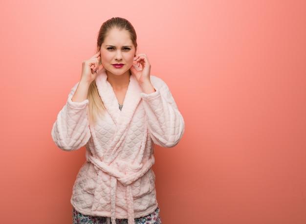 Молодая русская женщина в пижаме, закрывающей уши руками