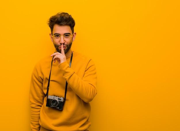 Молодой фотограф человек держит в секрете или просит молчать