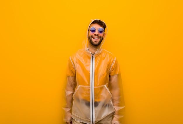 Молодой человек в плаще от дождя веселый с большой улыбкой