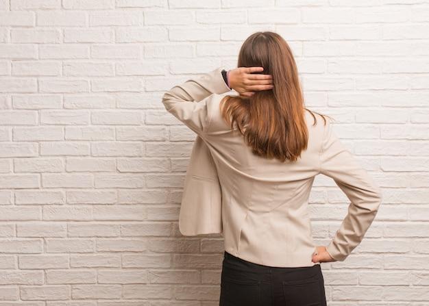 何かについて考えて後ろから若いかなりビジネス起業家の女性