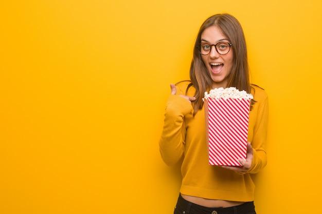 かなり白人の若い女性は驚いた、成功と繁栄を感じています。彼女はポップコーンを食べています。