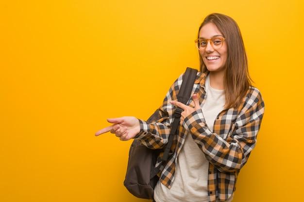 指で側を指している若い学生女性