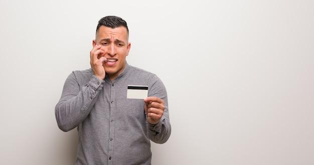 Молодой латинский мужчина держит кредитку, кусая ногти, нервный и очень взволнованный