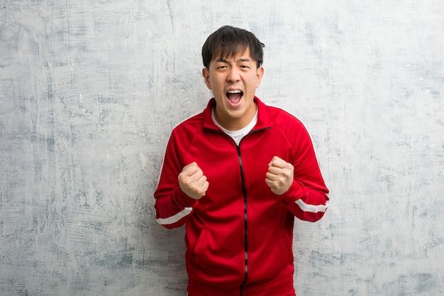 Молодой спортивный фитнес китаец удивлен и шокирован