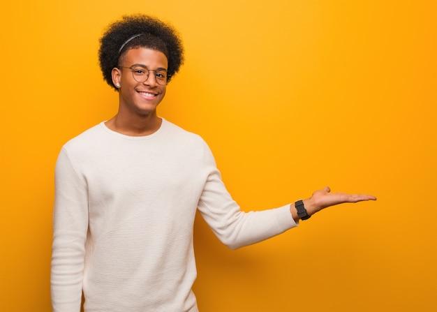 手で何かを保持しているオレンジ色の壁を越えて若いアフリカ系アメリカ人男性