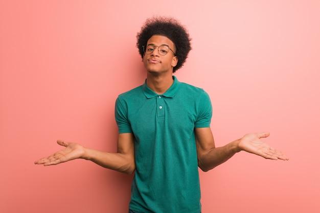 疑いと肩をすくめてピンクの壁を越えて若いアフリカ系アメリカ人