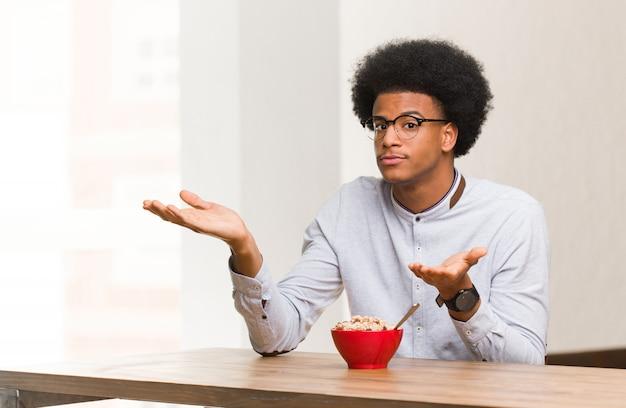 混乱して疑わしい朝食を食べている若い黒人男性