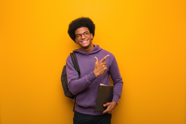 アフリカ系アメリカ人学生の若い男が指で側を指しています。