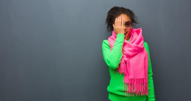 幸せな叫びと手で顔を覆っている青い目を持つ若いアフリカ系アメリカ人の女の子