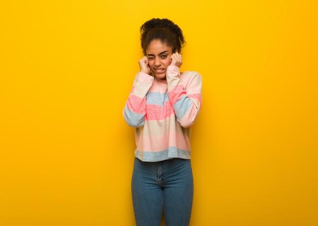Молодая черная афроамериканская девушка с голубыми глазами закрыла уши руками