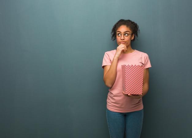 若い黒人女性は疑っていて混乱しています。彼女はポップコーンのバケツを持っています。