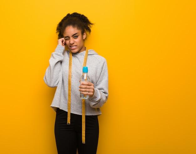 Молодой фитнес черная женщина, охватывающих уши руками. держать бутылку воды.