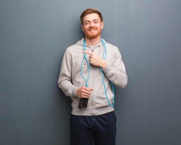 赤毛の若いフィットネス男が指で側を指しています。彼は縄跳びを持っています。