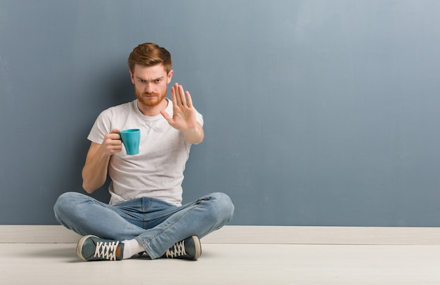 赤毛の若い男が前に手を入れて床に座っています。彼はコーヒーマグを持っています。