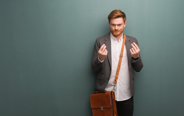 必要のジェスチャーをしている若い赤毛のビジネスマン