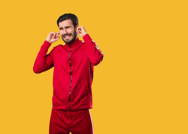 Молодой человек фитнес, охватывающих уши руками