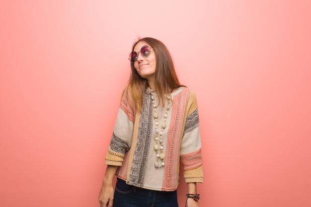 目標と目的を達成することを夢見てピンクの背景に若いヒッピー女性