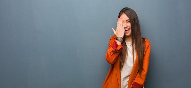 幸せな叫び手で顔を覆っている若い自然な女性