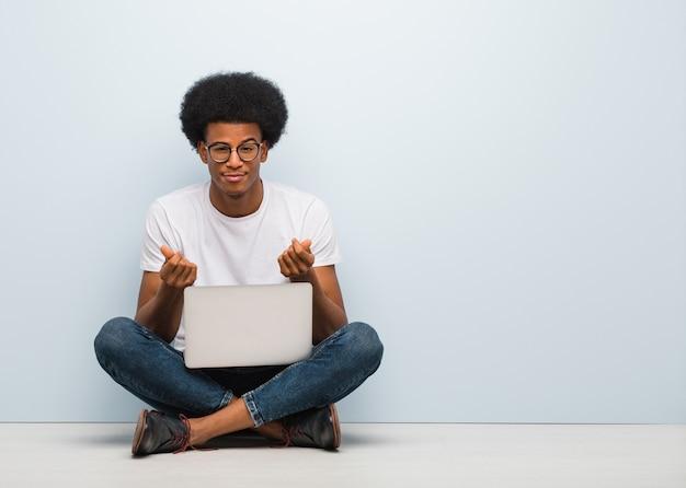 必要のジェスチャーをしているラップトップで床に座っている若い黒人男性