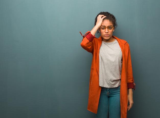 青い目を持つ若い黒アフリカ系アメリカ人の女の子は疲れていると非常に眠い