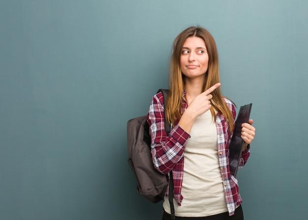 指で側を指している若い学生ロシア女性