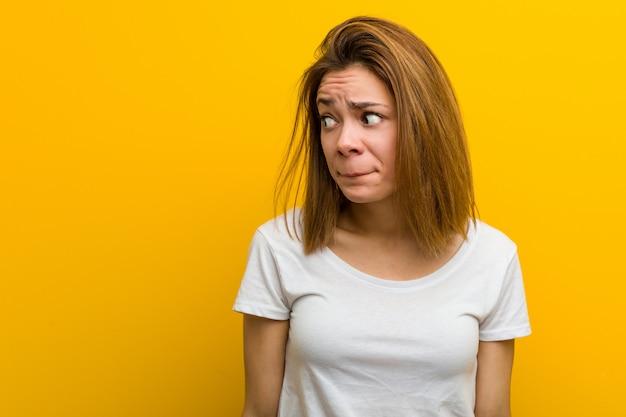 混乱している若い自然な白人女性は、疑わしくて自信がないと感じます。