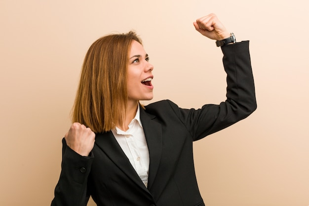 勝利、勝者の概念の後、彼女の拳を上げる若い白人女性。