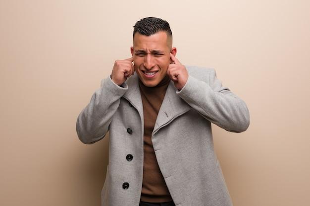 Молодой латинский бизнесмен покрывая уши руками