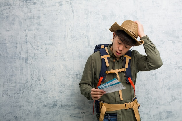 Молодой исследователь китайский мужчина держит билеты на самолет обеспокоены и перегружены