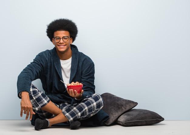 座っていると大きな笑顔で陽気な朝食を持っている若い黒人男性