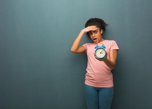物思いにふける若い黒人女性、何かを実感してください。彼女は目覚まし時計を持っています。