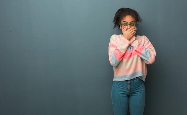 青い目を持つ若いアフリカ系アメリカ人の女の子は驚いてショックを受けました