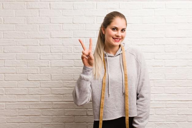 測定テープを保持している若いフィットネスロシア女性