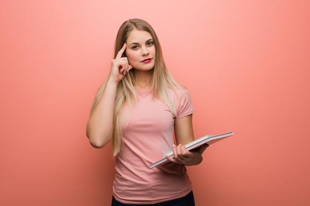 アイデアを考えて若いロシア美少女。彼女は本を持っています。