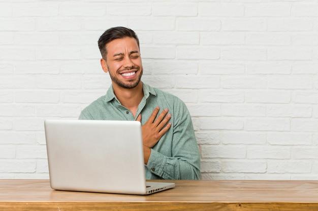 Работа молодого филиппинского человека сидя с его компьтер-книжкой смеясь над держащ руки на сердце, концепции счастья.