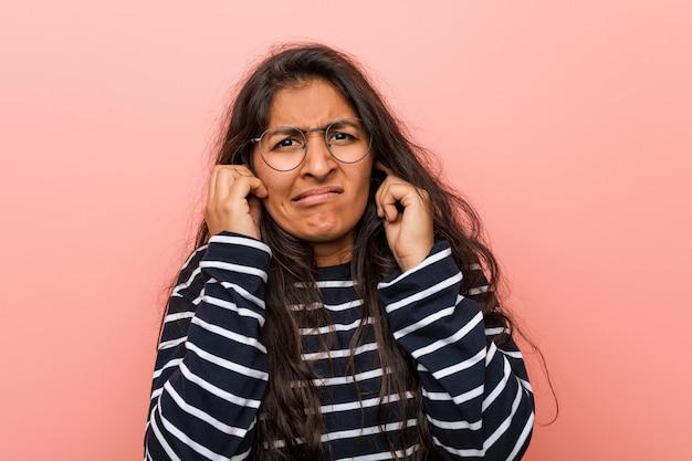 Молодая интеллектуальная индийская женщина, охватывающих уши своими руками.