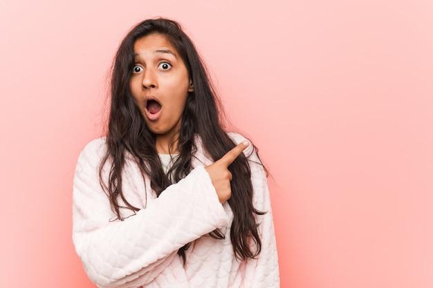 側を指しているパジャマを着ている若いインド人女性