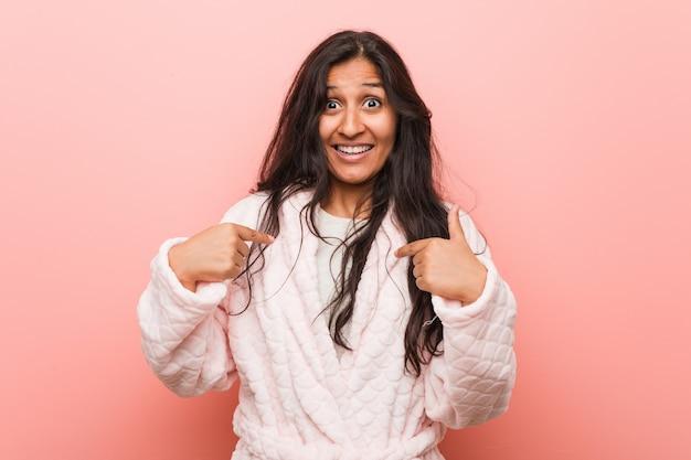 パジャマを着ている若いインド人女性は、広く笑って、自分自身を指して驚いた。
