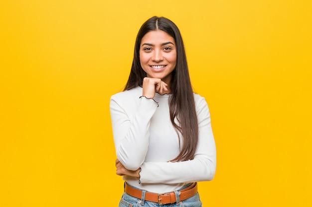 幸せで自信を持って、手であごに触れて黄色の背景に対して若い可愛いアラブ女性。