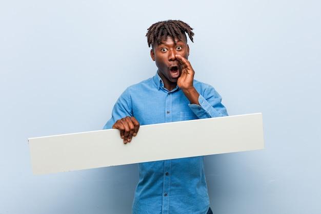 Молодой раста черный человек держит плакат с криком возбужденных на фронт.