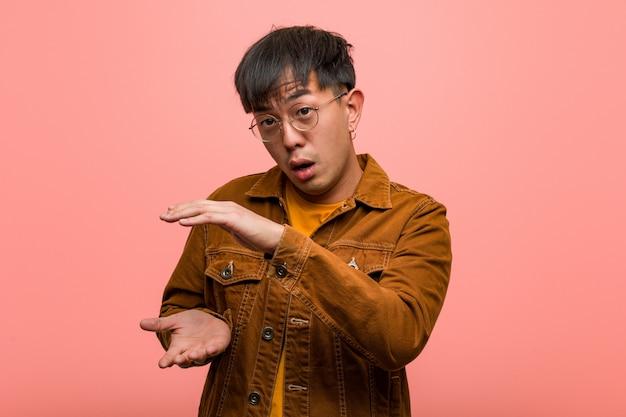 非常に驚いてショックを受けて何かを保持しているジャケットを着ている若い中国人男性