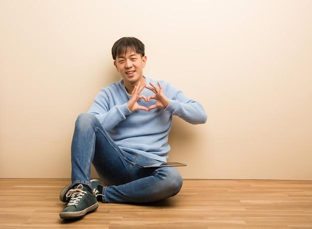 手でハートをしている彼のタブレットを使用して座っている若い中国人男性