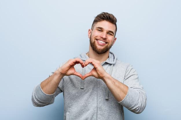 Молодой красивый человек фитнеса усмехаясь и показывая форму сердца с его руками.
