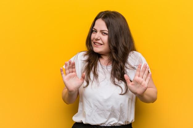 Молодые пышные плюс женщина размера, отвергая кого-то показывая жест отвращения.